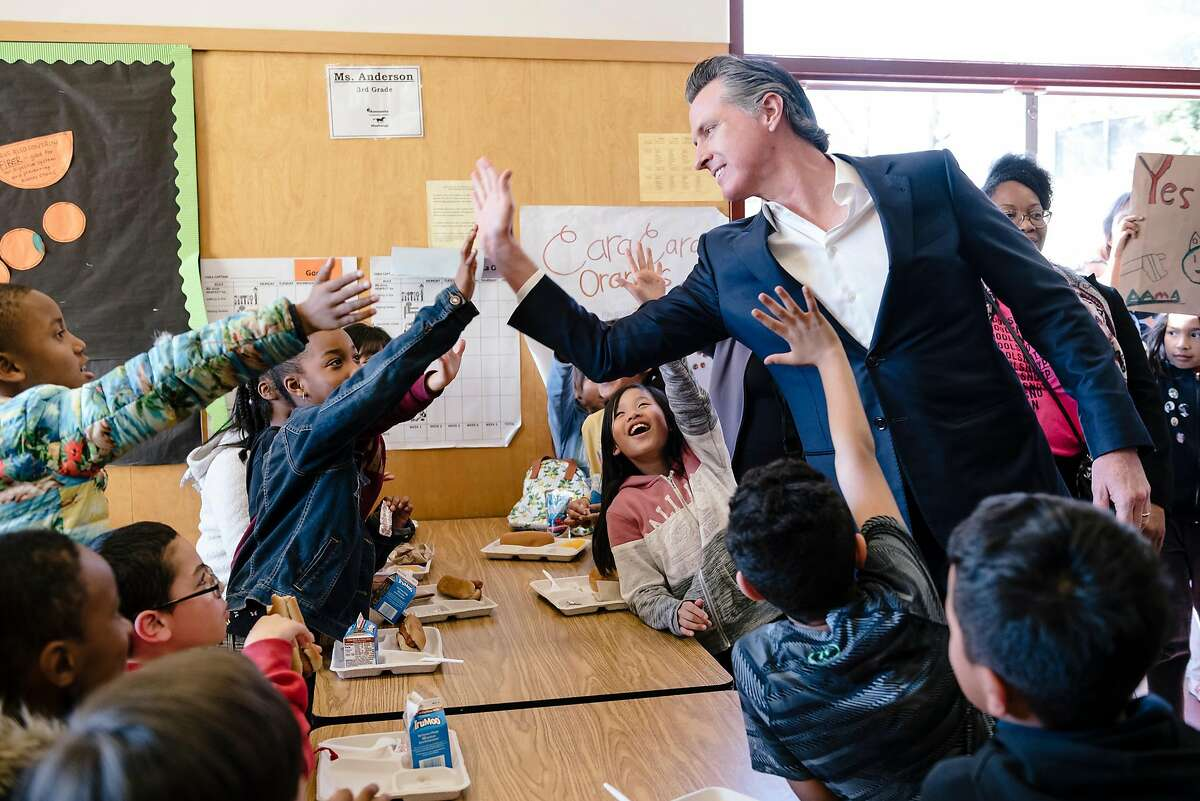 Gov. Gavin Newsom gives high-fives to students in the cafeteria during a campaign stop in support of state Proposition 13 at Manzanita SEED Elementary School in Oakland in March 2020.