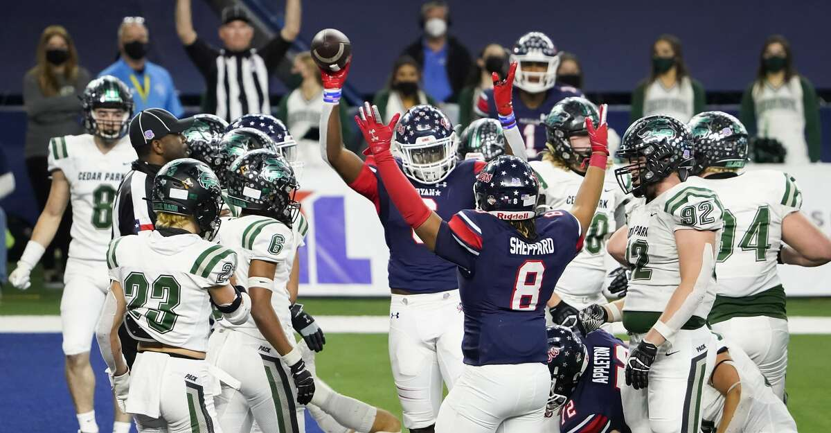 Denton Ryan's Anthony Hill Jr. celebrates with Jay Sheppard (8) after scoring on a short touchdown run against Cedar Park during the first half of the Class 5A Division I state football championship game Friday, Jan. 15, 2021, in Arlington, Texas. (Smiley N. Pool/The Dallas Morning News via AP)
