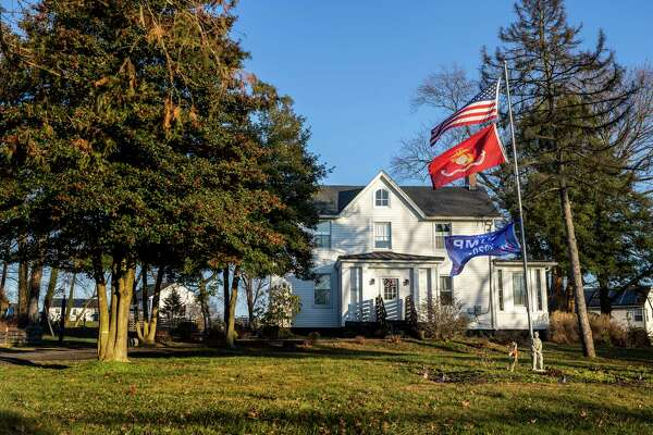 A home along Paradise Road in Aberdeen flies an American flag above a flag for the U.S. Marine Corps and a Trump campaign flag.