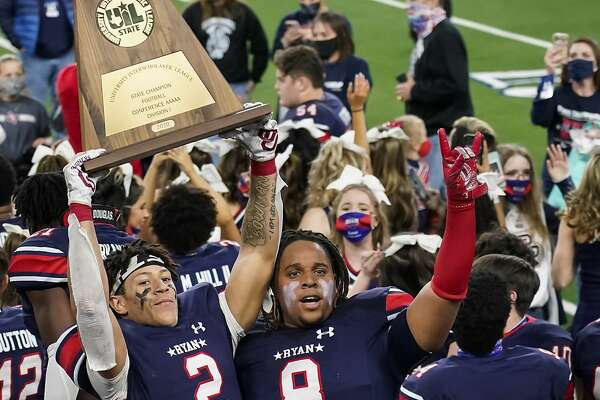Denton Ryan wide receiver Billy Bowman Jr. (2) hoists the championship trophy next to Jay Sheppard (8) after the team's win over Cedar Park in the Class 5A Division I state football championship game Friday, Jan. 15, 2021, in Arlington, Texas. (Smiley N. Pool/The Dallas Morning News via AP)