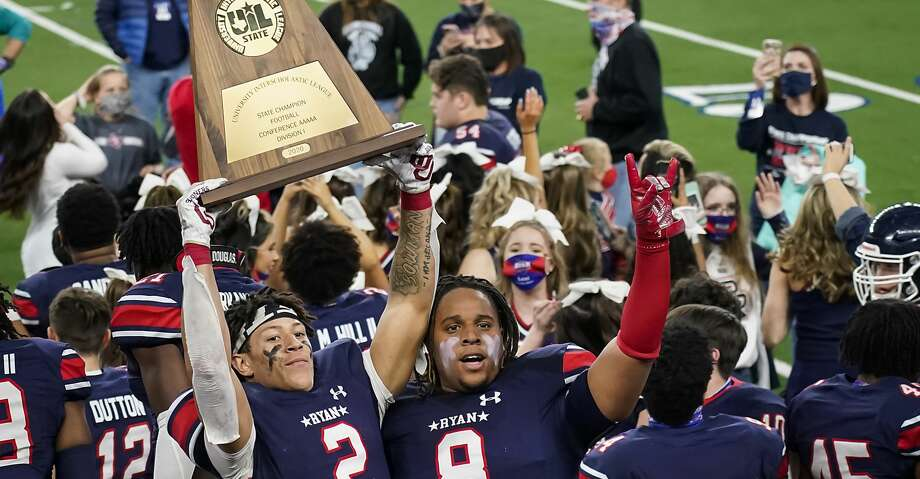 Denton Ryan wide receiver Billy Bowman Jr. (2) hoists the championship trophy next to Jay Sheppard (8) after the team's win over Cedar Park in the Class 5A Division I state football championship game Friday, Jan. 15, 2021, in Arlington, Texas. (Smiley N. Pool/The Dallas Morning News via AP) Photo: Smiley N. Pool/Associated Press / The Dallas Morning News
