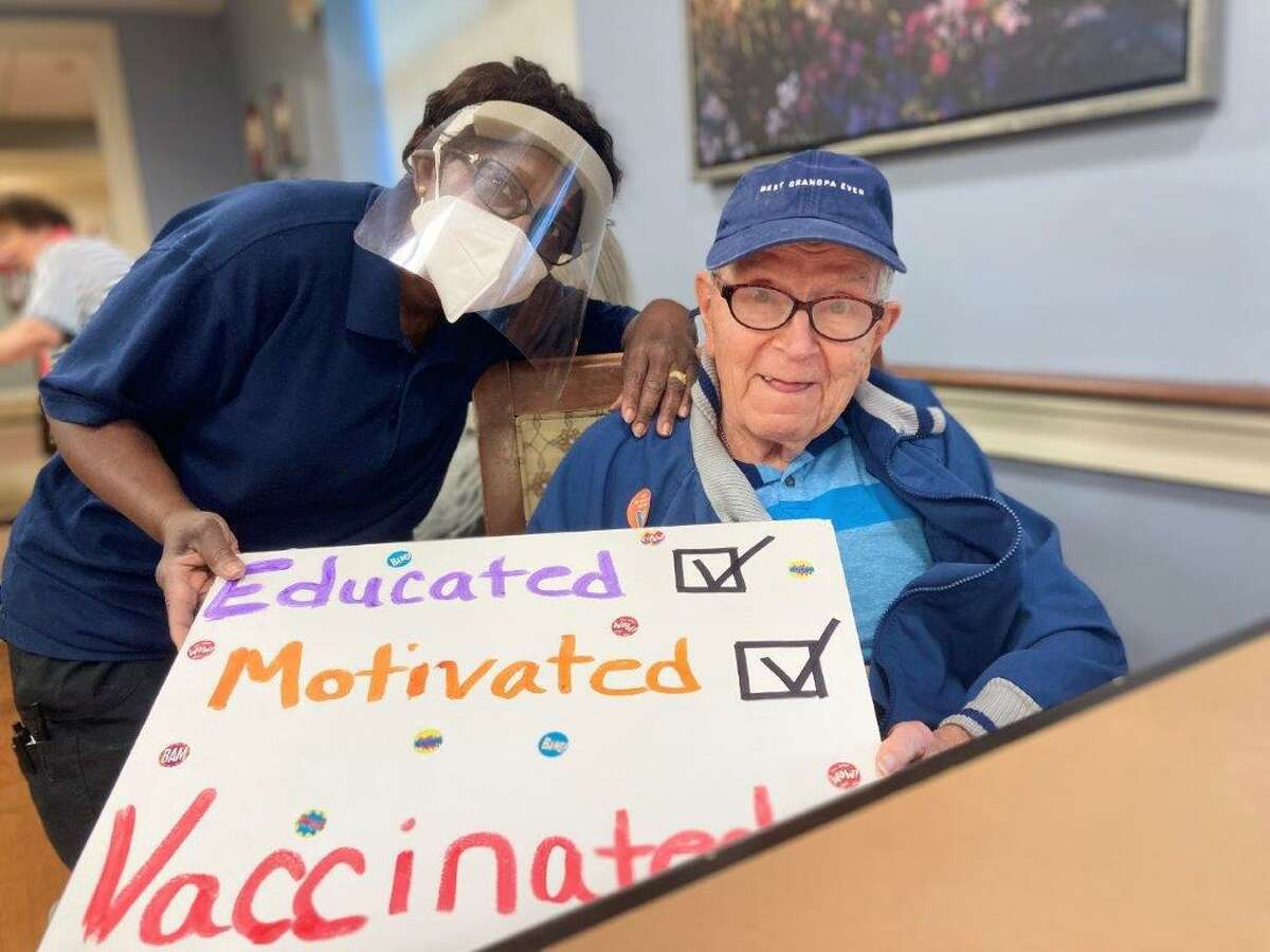 Benchmark Senior Living at Split Rock resident care associate Virginia Toussaint and facility resident Frank Hmelovsky on Wednesday, Jan. 13. Residents and staff at the facility received the COVID-19 vaccine that day.