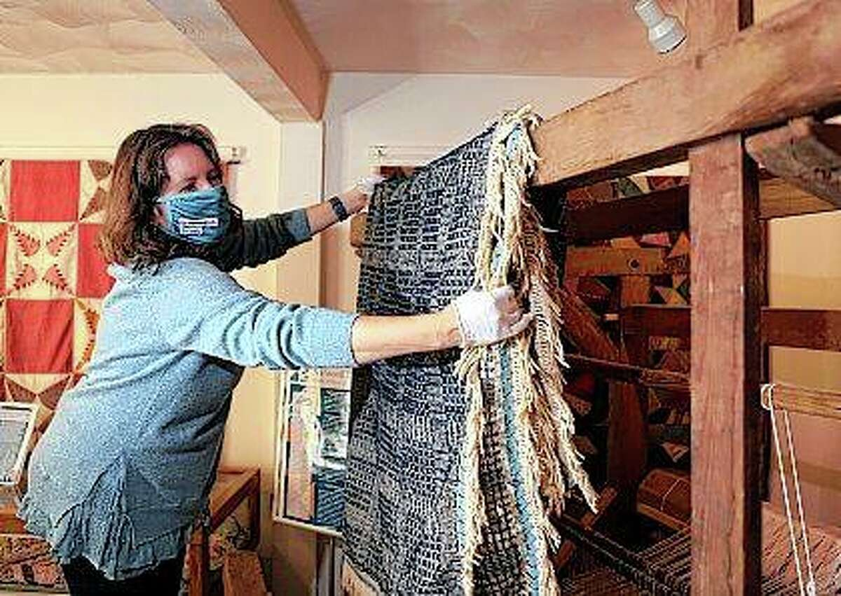 Montgomery Museum of Art & History curator Sherry Wyatt drapes a slave-made coverlet on a period loom in Christiansburg, Virginia. Although enslaved people worked in every aspect of the textile industry in antebellum America, individual pieces made by them are rarely verified and very few exist in museum collections today.