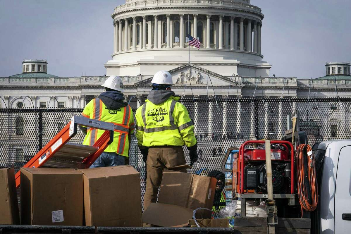 Workers install barbed wire on the fenced perimeter of the U.S. Capitol in Washington, D.C., on Jan. 15, 2021.