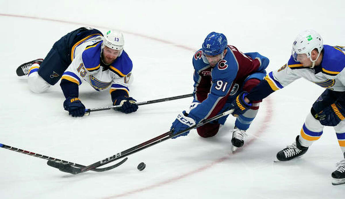 The Avalanche's Nazem Kadri (91) fights for control of the puck with the Blues' Kyle Clifford (left) and Ivan Barbashev in the first period Friday night in Denver.