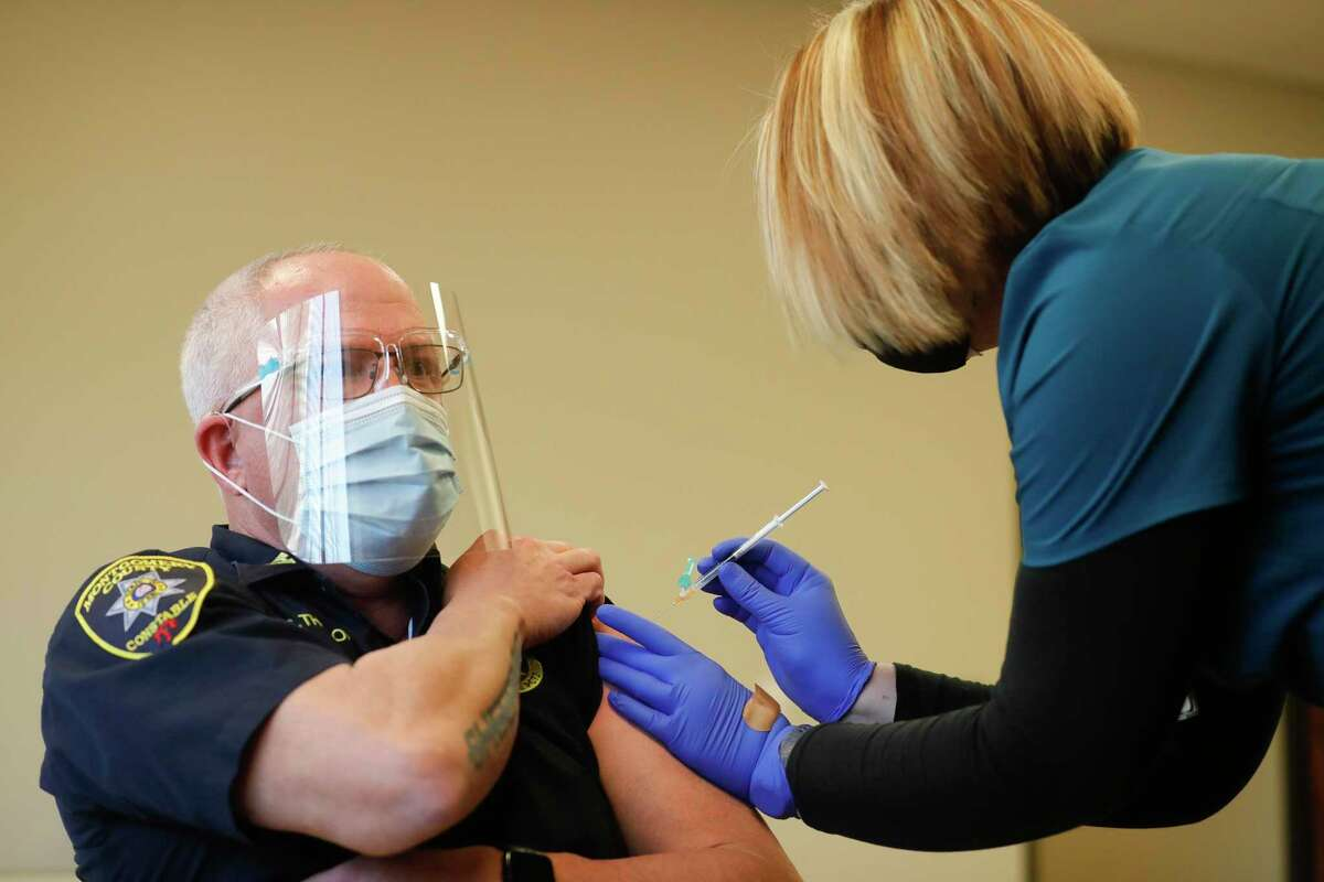 Cpt. Greg Thomason with the Montgomery County Precinct 2 Constable's Office receives his first dose of the Moderna COVID-19 vaccine at the Montgomery County Wellness Center, Thursday, Jan. 14, 2021, in Conroe.