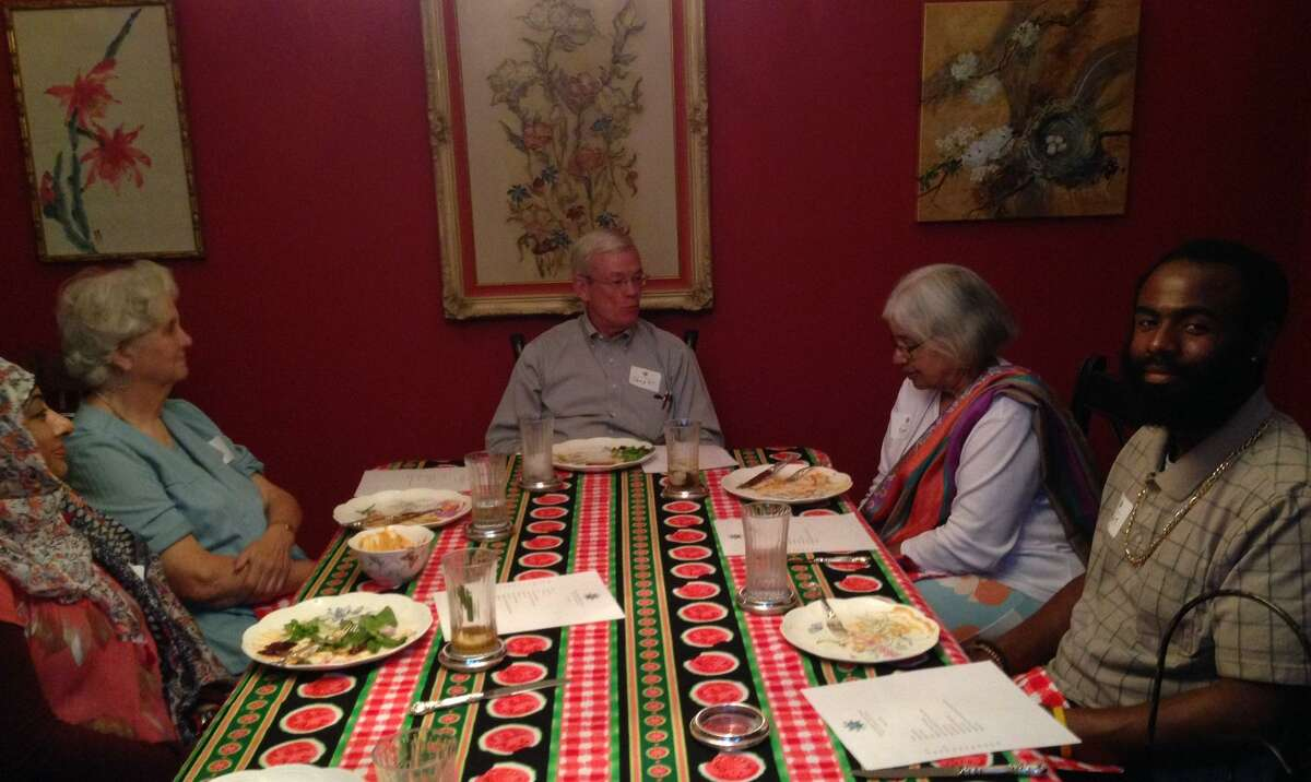In this photo from before the pandemic, members of the Spring Interfaith Council talk over a meal.