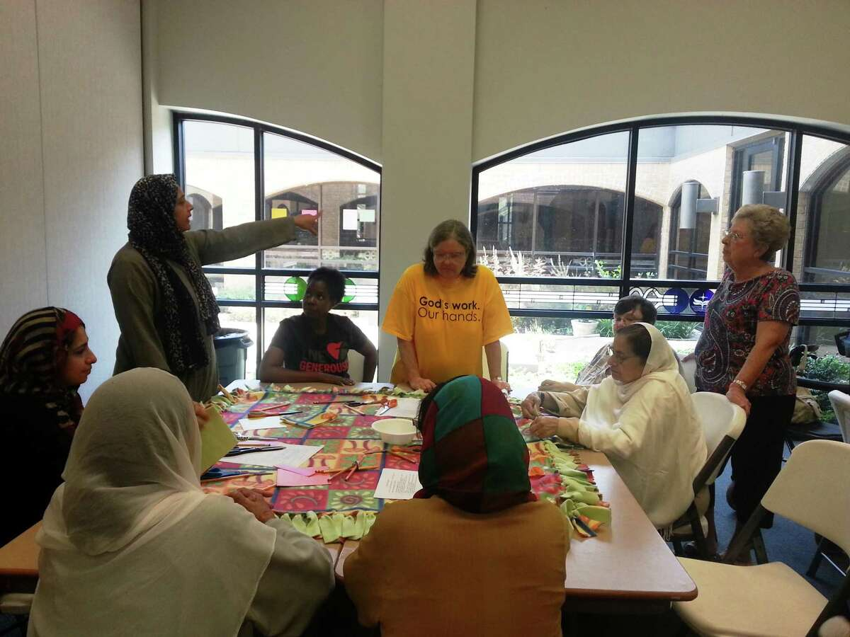 Interfaith women making blankets for the homeless at an event prior to the pandemic.