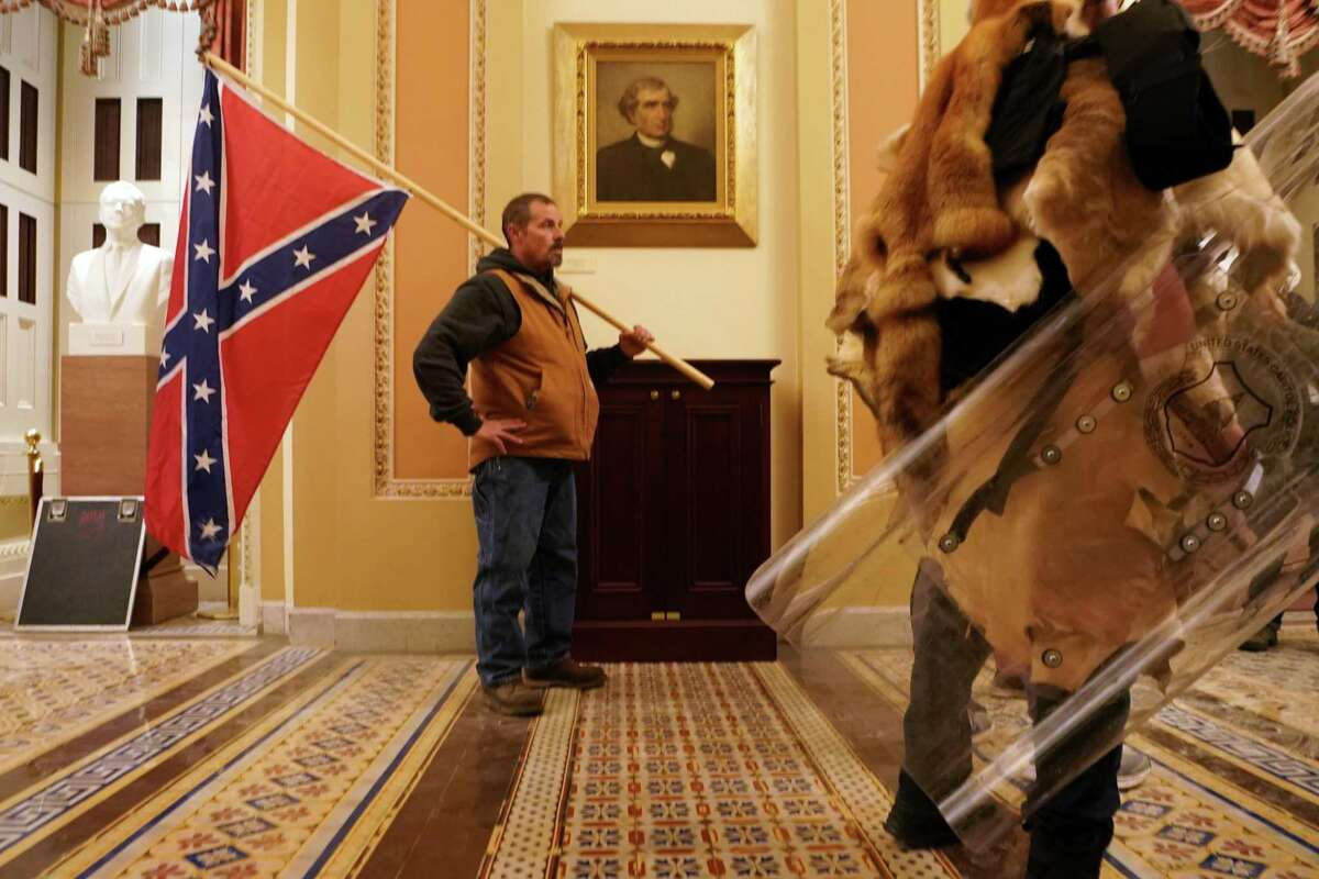 A man carries a Confederate flag as a mob protests the presidential election results, inside the Capitol in Washington on Wednesday, Jan. 6, 2021. The Trump era has been marked by open expressions of racial bigotry. (Erin Schaff/The New York Times)
