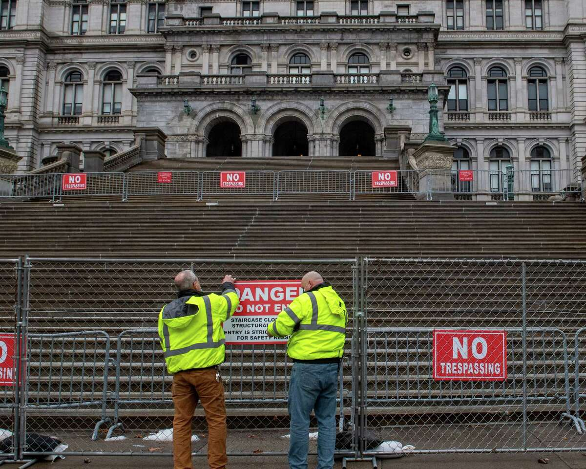 State Office of General Service workers, who could not give their names, hang a sign on a newly installed fence at the New York State Capitol building in Albany, NY, warning people the stairs are structurally unstable on Saturday, Jan. 16, 2021 (Jim Franco/special to the Times Union.)