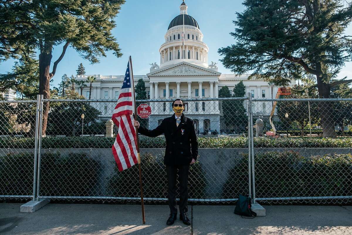 Christian Alvarado of Sacramento stands at attention with an American flag in front of the State Capital in Sacramento on Saturday, January 16, 2021. Alvaradro said that he was there to stand in solidarity with the legislatures.