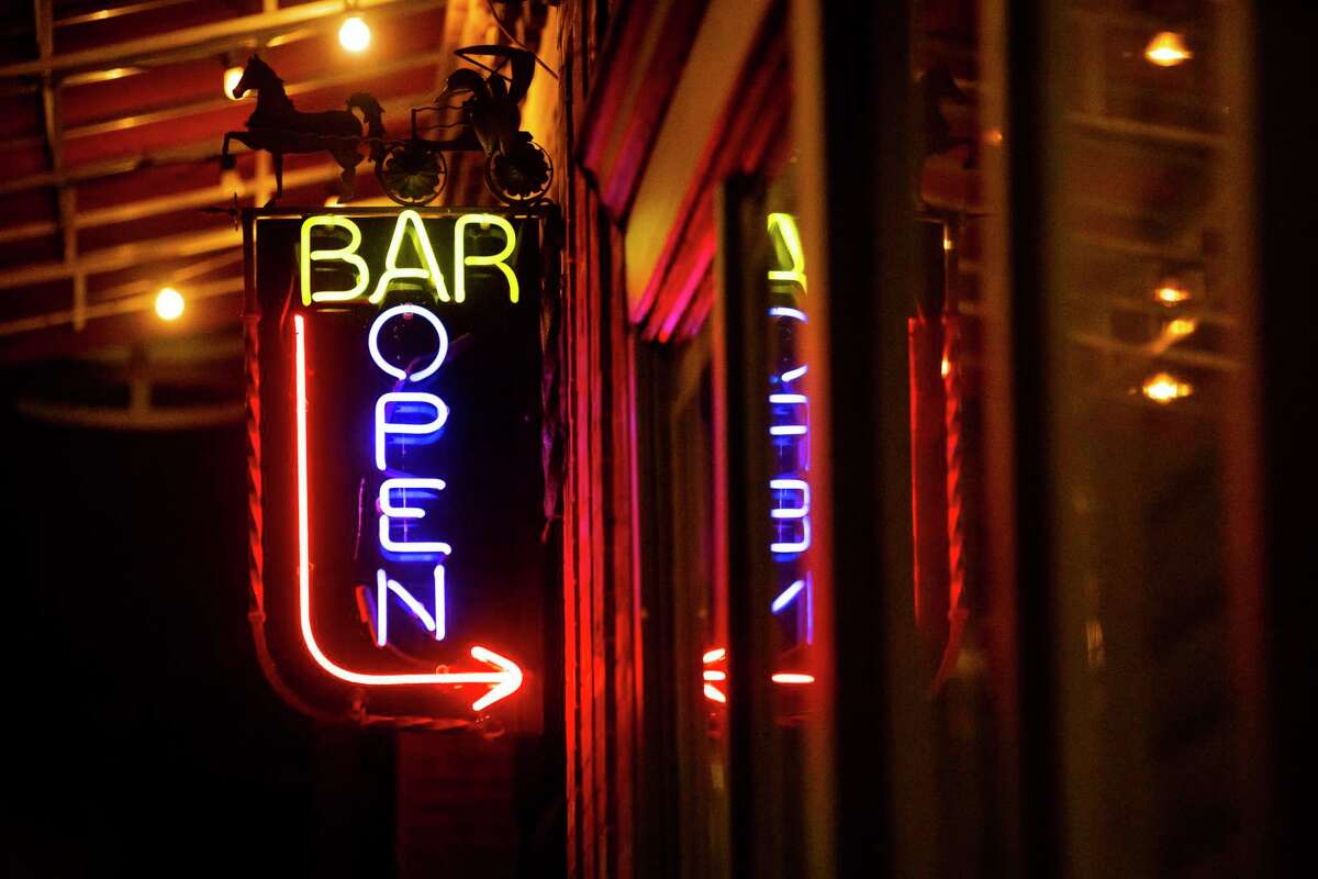 """A """"Bar Open"""" sign lights the way to a bar along Main Street on Thursday, Jan. 14, 2021, in downtown Houston."""