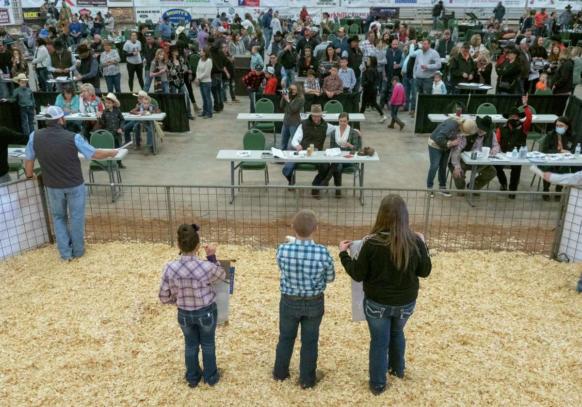 Lance Griffith, center, shows his Grand Champion Poultry 01/16/2021 during the auction at the 2021 Midland County Livestock Association Show at the Midland County Horseshoe Arena. Tim Fischer/Reporter-Telegram