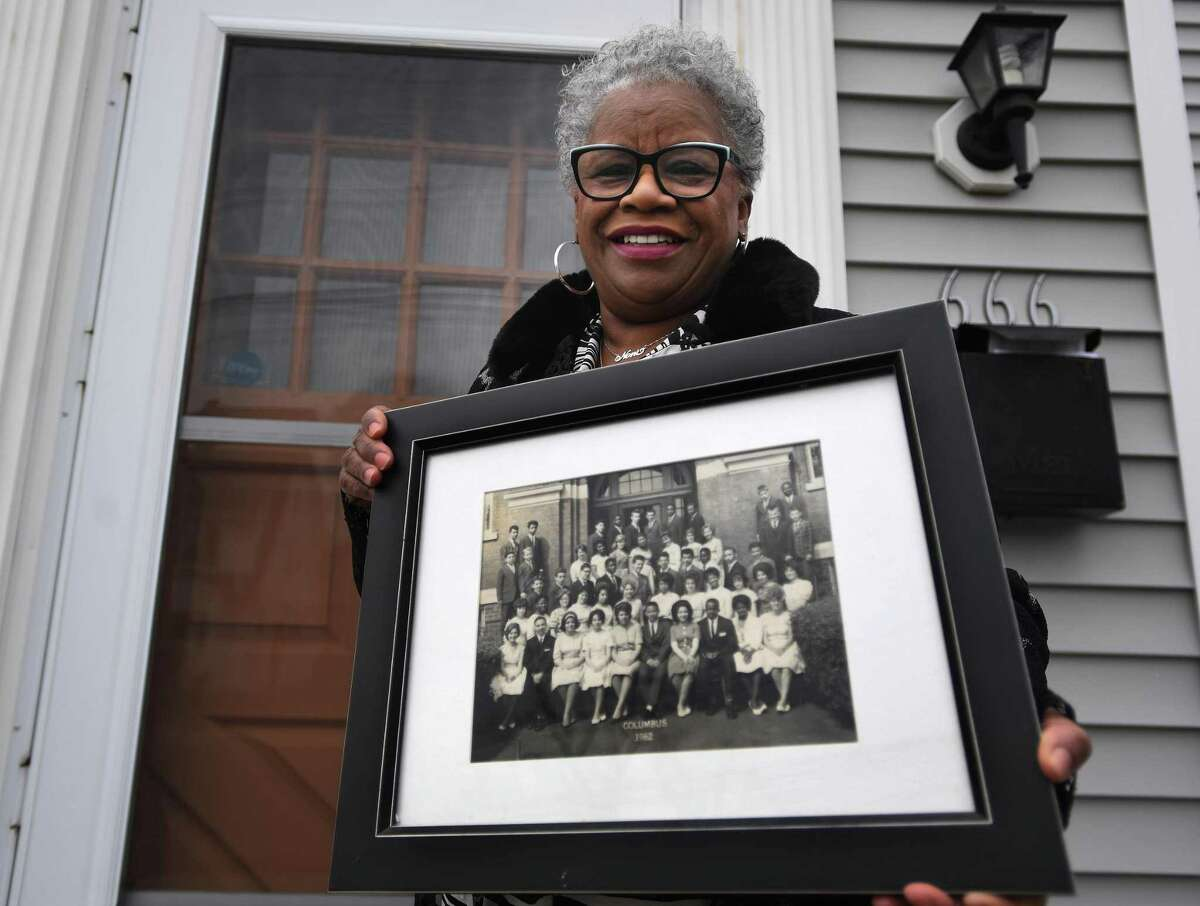 State Senator Marilyn Moore holds the photo of her 8th grade 1962 graduating class from Columbus School in Bridgeport, Conn. on Thursday, January 14, 2021. At Columbus, Moore met teacher and civil rights activist Charles Tisdale, who introduced her to the movement.