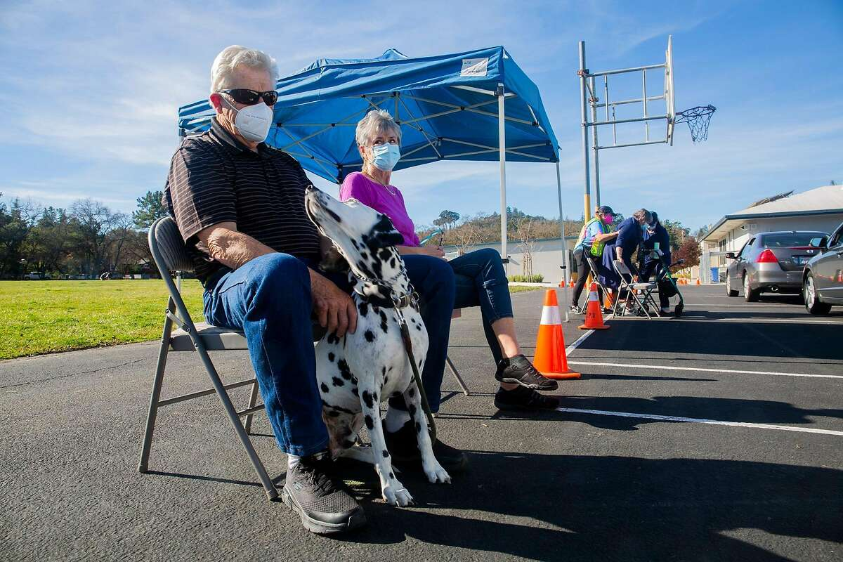 Don and Carol Franklin, 75 and 73, wait 30 minutes during post-vaccination observation alongside their dog, Ace, at the Stanley Middle School parking lot in Lafayette.