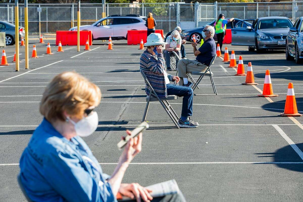 Elderly vaccinated patients sit and wait 30 minutes for a post vaccination observation period while chatting with their relatives on speaker phone at the Stanley Middle School Parking Lot Drive thru Vaccination center on Janurary 16, 2021 in Lafayette, CA.