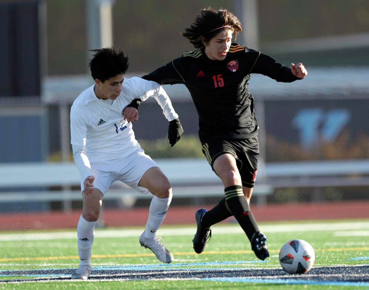 Oak Ridge's Edgar Chabes (12) battles for the ball against Caney Creek's Uvaldo Lozano (15) in the first period of a soccer match during the Humble ISD Bayou City Classic at Kingwood High School, Friday, Jan. 15, 2021, in Kingwood.