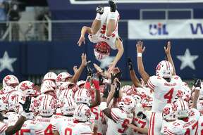 Katy defensive back Colton Cable (32) is tossed into the air by his teammates before the Class 6A Division II UIL State Championship high school football game against Cedar Hill at AT&T Stadium Saturday, Jan. 16, 2021, in Arlington, Texas. Katy captured the championship with a 51-14 win over Cedar Hill.