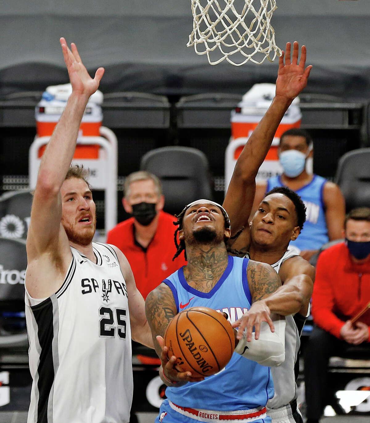 Jakob Poeltl #25 of the San Antonio Spurs and Devin Vassell #24 block shot of Ben McLemore #16 of the Houston Rockets. Rockets v Spurs at AT&T Center on Saturday, Jan. 16, 2021