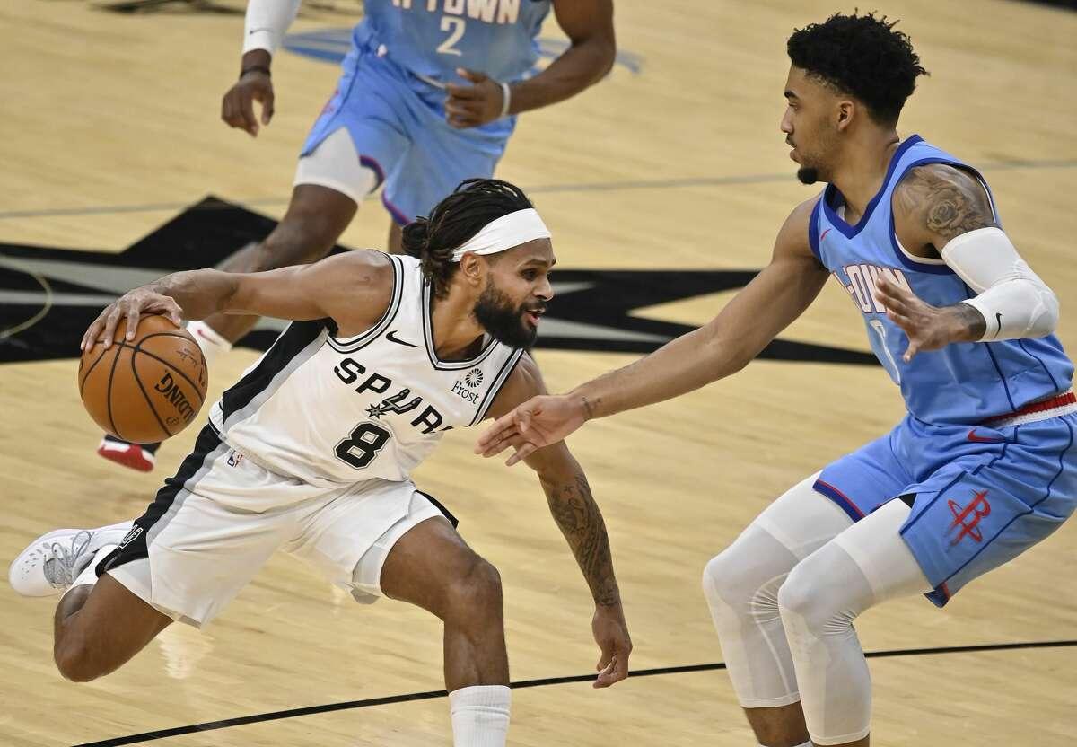 San Antonio Spurs' Patty Mills (8) drives against Houston Rockets' K.J. Martin during the first half of an NBA basketball game, Saturday, Jan. 16, 2021, in San Antonio. (AP Photo/Darren Abate)