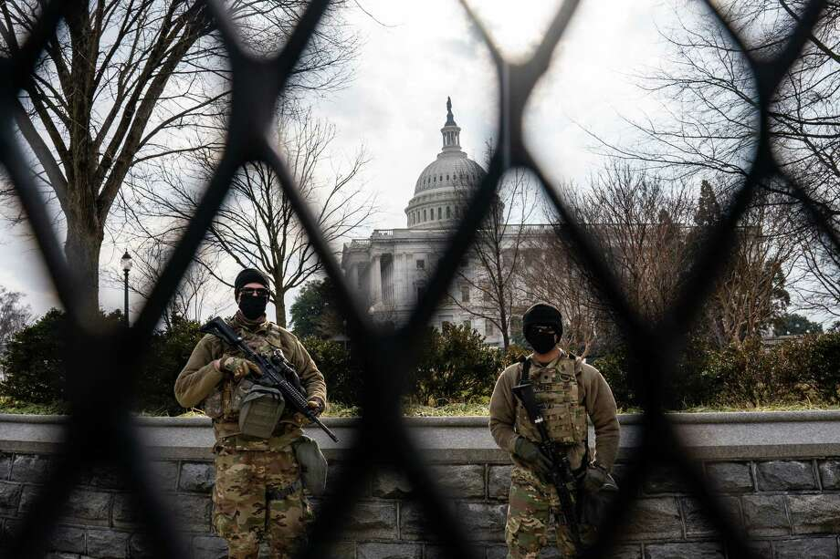 Members of the National Guard are seen behind a security fence at the U.S. Capitol on Friday. Photo: Washington Post Photo By Salwan Georges. / The Washington Post