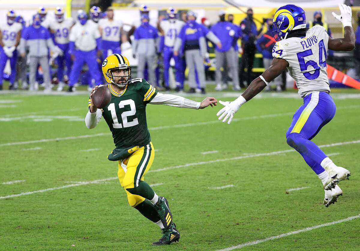 Aaron Rodgers eludes the Rams' Leonard Floyd on a 1-yard score in the second quarter. The last Green Bay quarterback to run for a TD in a playoff game at Lambeau: Bart Starr.