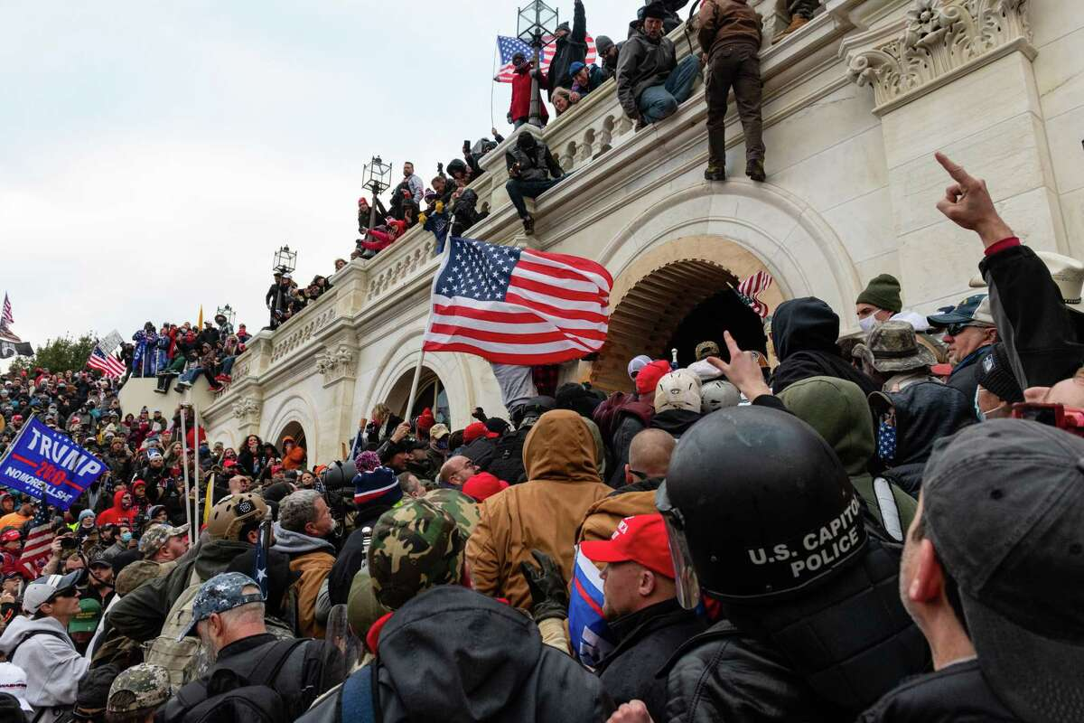 Demonstrators attempt to enter the U.S. Capitol building during a protest in Washington, D.C., U.S., on Wednesday, Jan. 6, 2021. The U.S. Capitol was placed under lockdown and Vice President Mike Pence left the floor of Congress as hundreds of Demonstrators swarmed past barricades surrounding the building where lawmakers were debating Joe Biden's victory in the Electoral College. Photographer: Eric Lee/Bloomberg