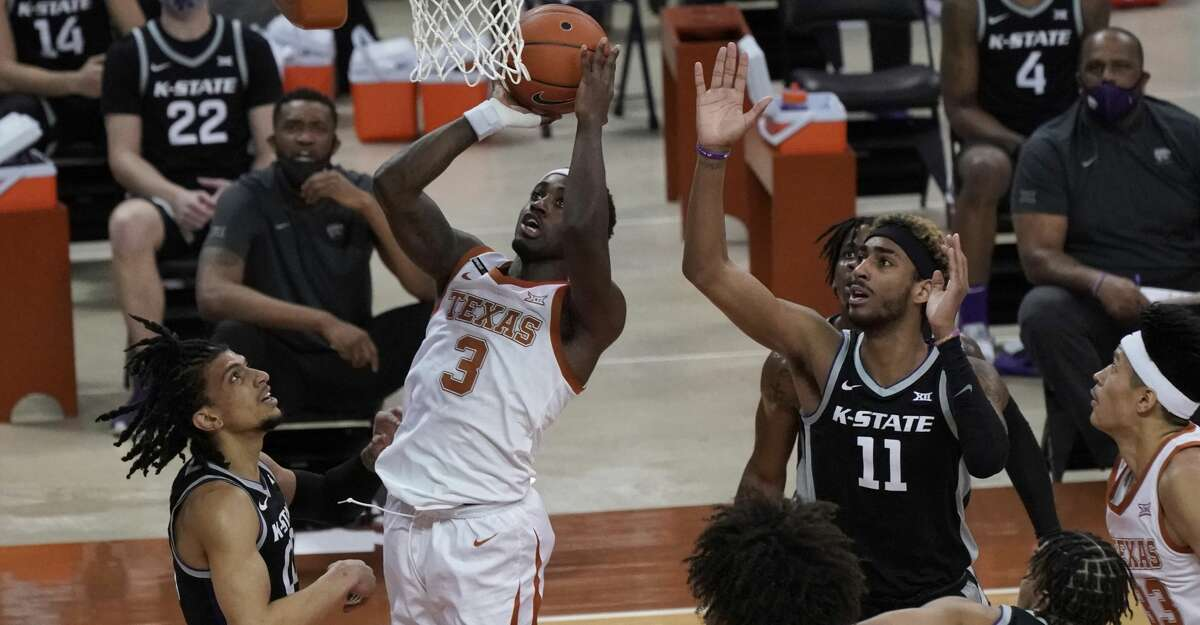 Texas' Courtney Ramey (3) drives to the basket against Kansas State's Mike McGuirl, left, and Antonio Gordon, right, during the first half of an NCAA college basketball game in Austin, Texas, Saturday, Jan. 16, 2021. (AP Photo/Chuck Burton)