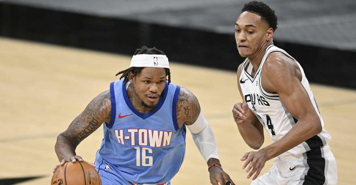 Houston Rockets' Ben McLemore (16) drives against San Antonio Spurs' Devin Vassell during the second half of an NBA basketball game, Saturday, Jan. 16, 2021, in San Antonio. (AP Photo/Darren Abate)