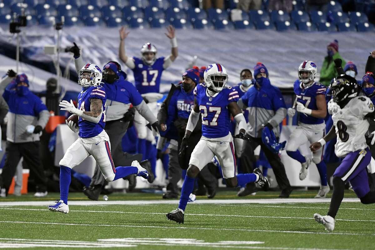 Bills cornerback Taron Johnson (left) heads for the end zone after intercepting a pass from Ravens quarterback Lamar Jackson (8). Johnson's touchdown return was 101 yards.