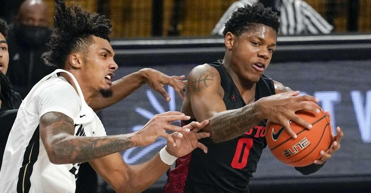 Houston guard Marcus Sasser (0) grabs a rebound in front of Central Florida guard Brandon Mahan, left, during the first half of an NCAA college basketball game, Saturday, Dec. 26, 2020, in Orlando, Fla. (AP Photo/John Raoux)