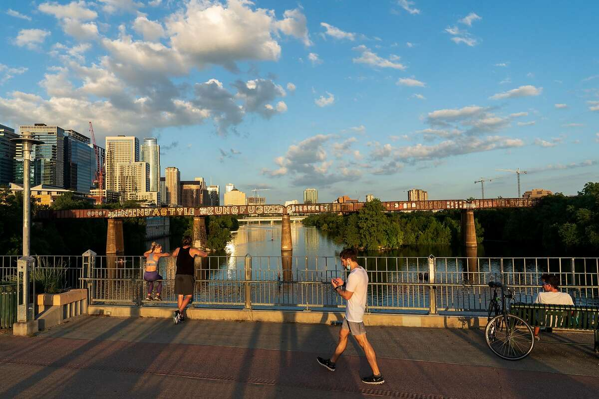 Pedestrians walk on the Pfluger Pedestrian Bridge in downtown Austin on July 10, 2020.