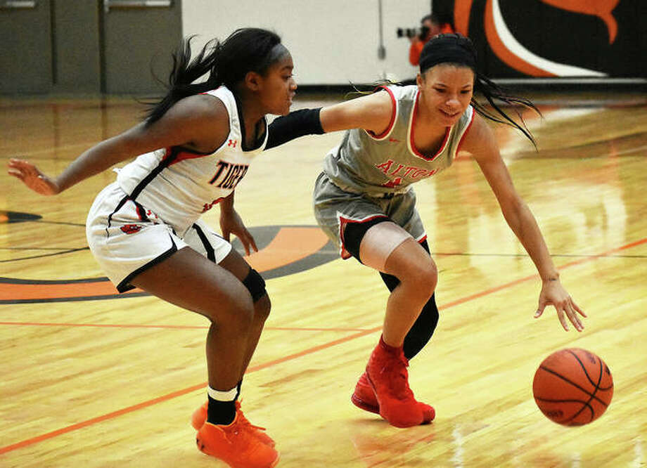 Alton's Khaliyah Goree (right) handles the ball against pressure from Edwardsville's Quierra Love during last season's SWC girls basketball game in January at Lucco-Jackson Gym in Edwardsville. Photo: Matt Kamp / Hearst Illinois
