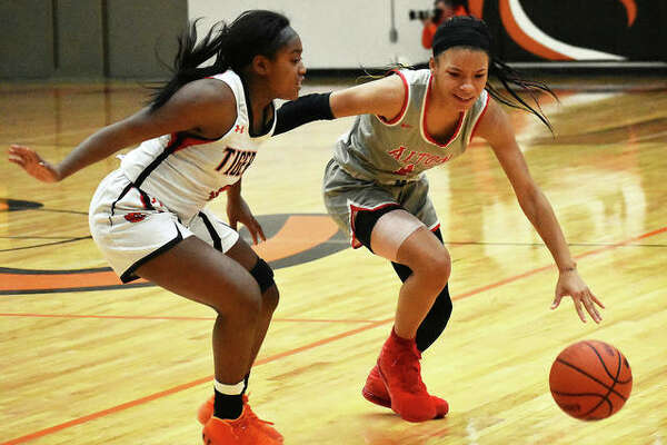 Alton's Khaliyah Goree (right) handles the ball against pressure from Edwardsville's Quierra Love during last season's SWC girls basketball game in January at Lucco-Jackson Gym in Edwardsville.