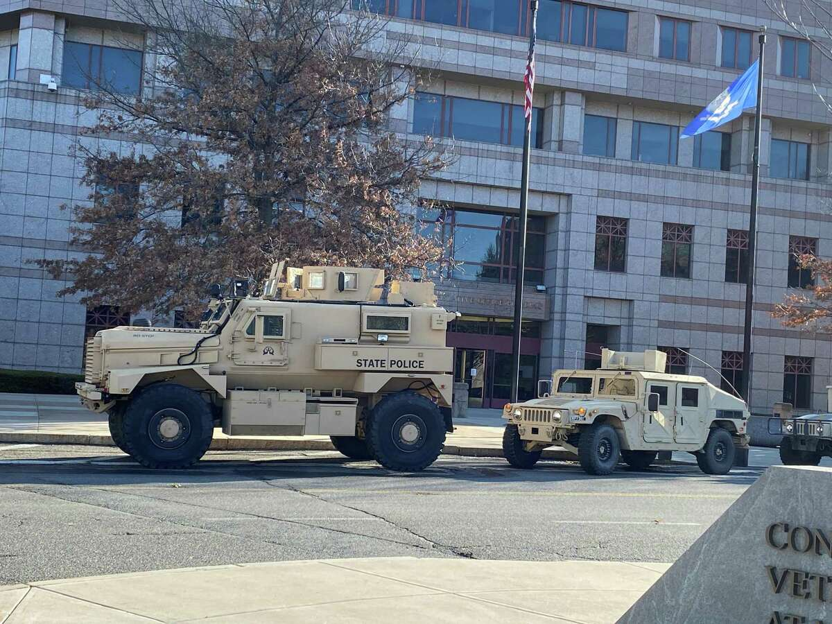 State Police tactical vehicles are parked next to the Legislative Office Building in Hartford on Sunday morning in case they are needed. Protests were planned at many statehouses across the nation.