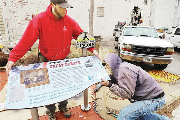 Lance Arrow, left, and Dan Slightom, from Arrow Outdoor Signs and Advertising, work to install a replacement marker at the corner of Broadway and State Street in Alton. The previous sign, part of about 10 historical markers tracking buildings and other area of interest related to the 1858 Lincoln-Douglas debate, was destroyed by the semi-great Flood of 2019. This particular marker identifies the nearby building that once housed the Franklin House hotel, which was used as Abraham Lincoln's debate headquarters.