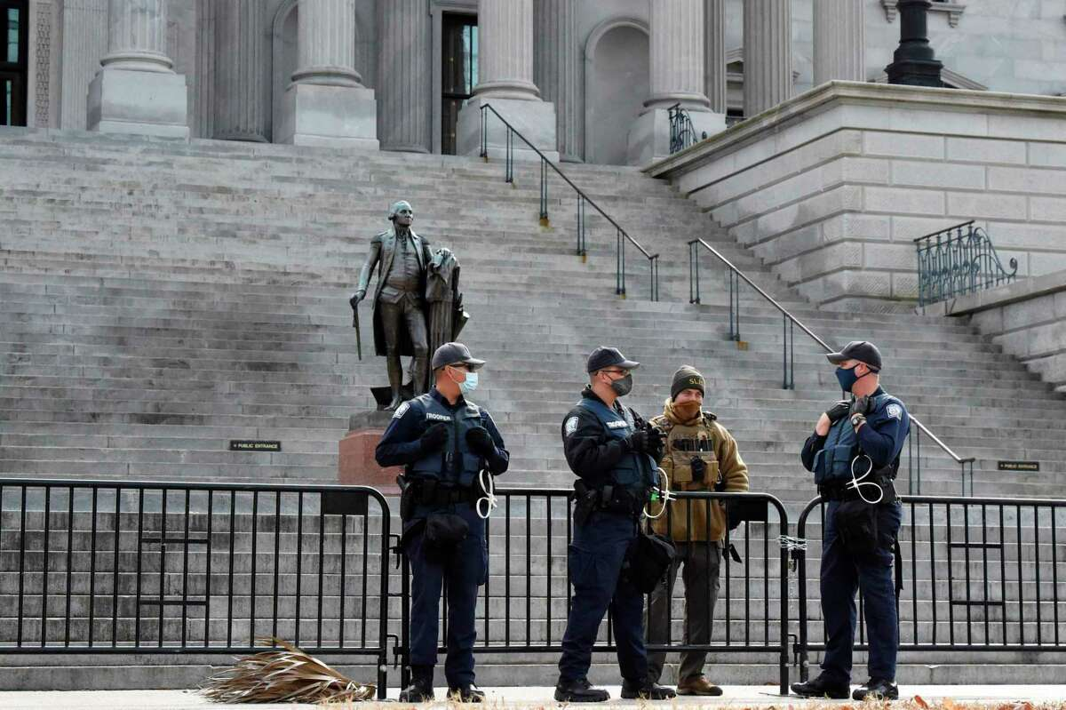 Law enforcement officers stand watch at South Carolina's Statehouse during an expected day of unrest across the country on Sunday, Jan. 17, 2021, in Columbia, S.C.