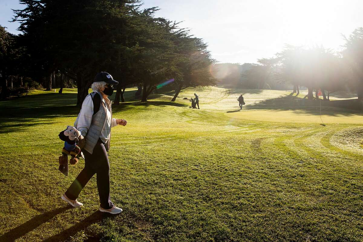 """Calista Shea, 92, carries her golf bag across the course to the tee at Golden Gate Park Golf Course in San Francisco, Calif. Friday, January 15, 2021. Shea is 92 and still carries her own golf bag while walking the course every Friday morning with a group of senior golfers dubbed the """"Senior Swingers""""."""