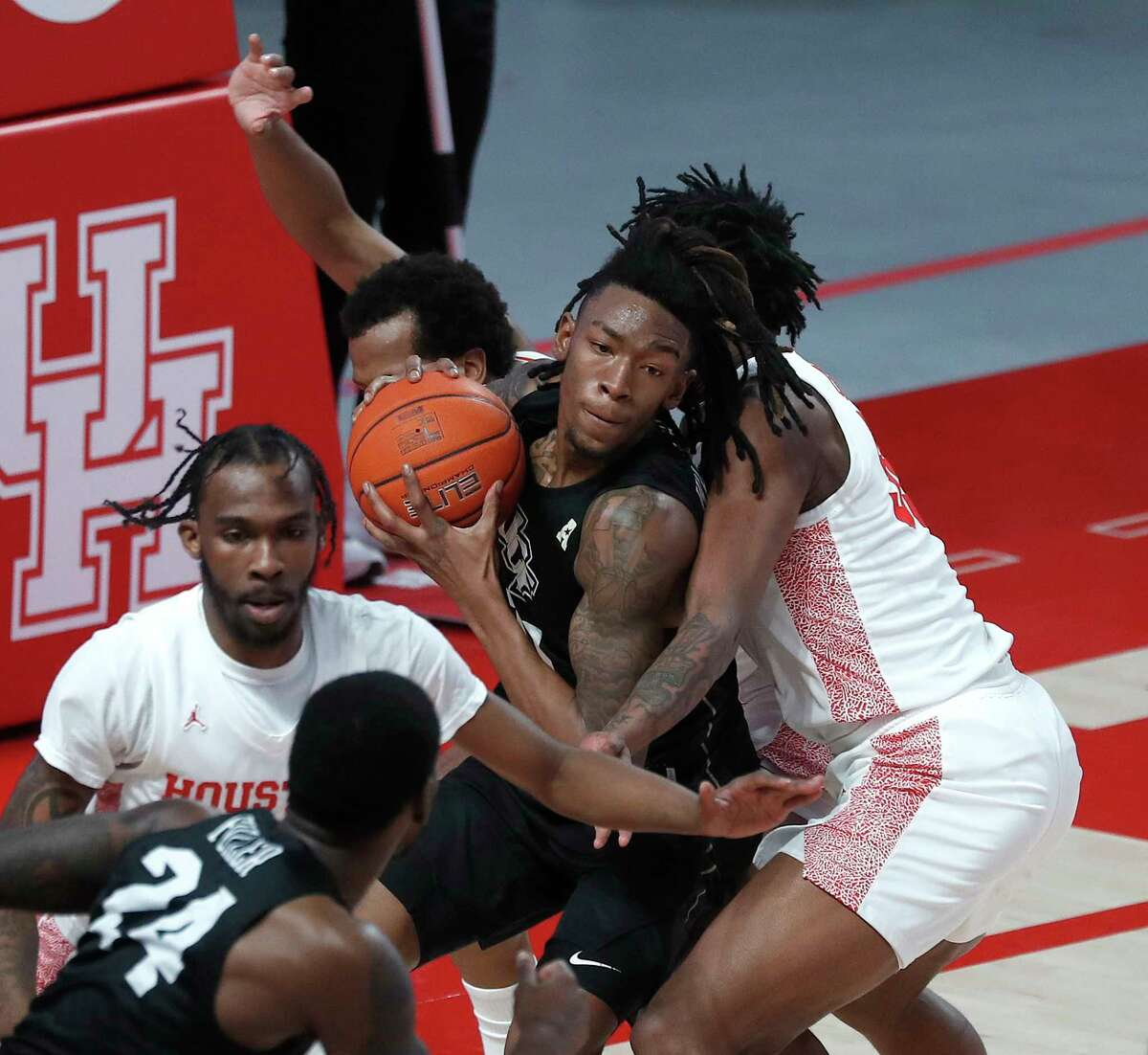 UCF Knights forward C.J. Walker (21) is surrounded by Houston Cougars during the first half of a men's NCAA basketball game at the Fertitta Center, in Houston, Sunday, Jan. 17, 2021.