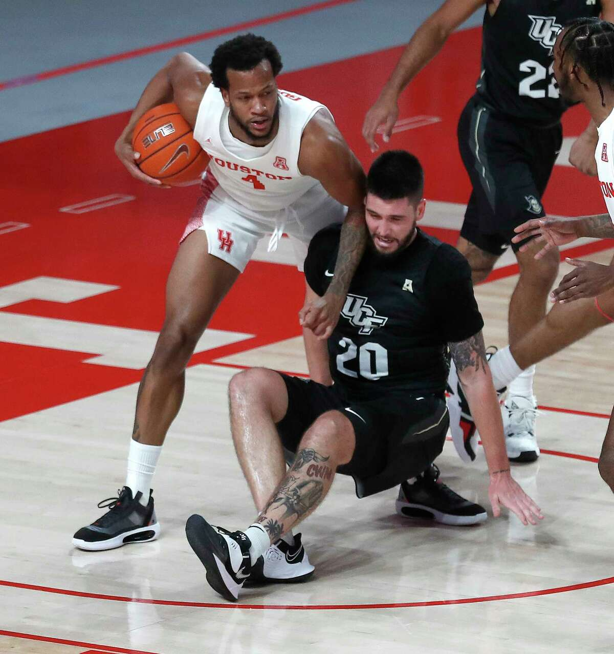 Houston Cougars forward Justin Gorham (4) battles against UCF Knights forward Sean Mobley (20) during the first half of a men's NCAA basketball game at the Fertitta Center, in Houston, Sunday, Jan. 17, 2021.