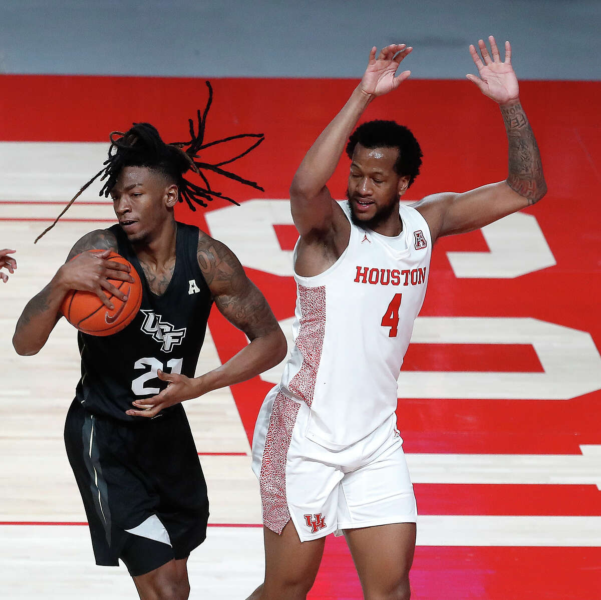 UCF Knights forward C.J. Walker (21) grabs the rebound from Houston Cougars forward Justin Gorham (4) during the second half of a men's NCAA basketball game at the Fertitta Center, in Houston, Sunday, Jan. 17, 2021.