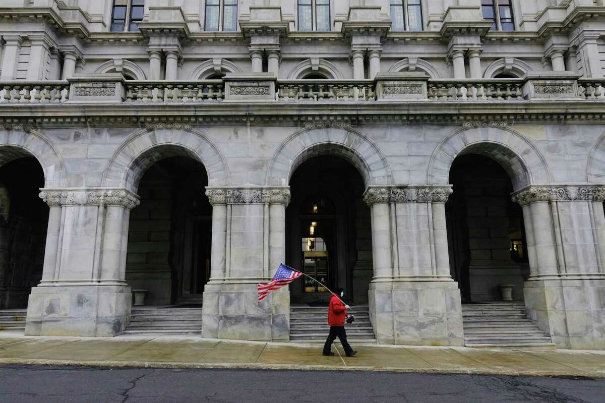 A Capital Region resident, who did not want to give his name, walks around the capitol building on Sunday, Jan. 17, 2021, in Albany, N.Y. The man said that he came down to walk because he wanted to send the message that'