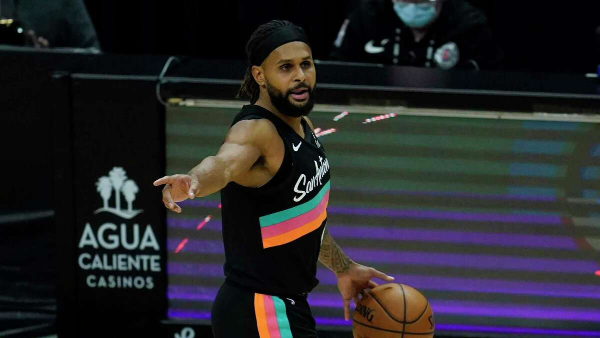San Antonio Spurs guard Patty Mills (8) points to a teammate during the third quarter of an NBA basketball game against the Los Angeles Clippers Tuesday, Jan. 5, 2021, in Los Angeles. (AP Photo/Ashley Landis)