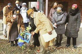 At the 41st annual commemoration of Rev. Dr. Martin Luther King, Jr., Day on Sunday, Rosetta Brown, left, and Michael Holiday, right, place a wreath in James H. Killion Park at Salu as about 100 people watch. Joining them were members of the Alton NAACP executive committee.