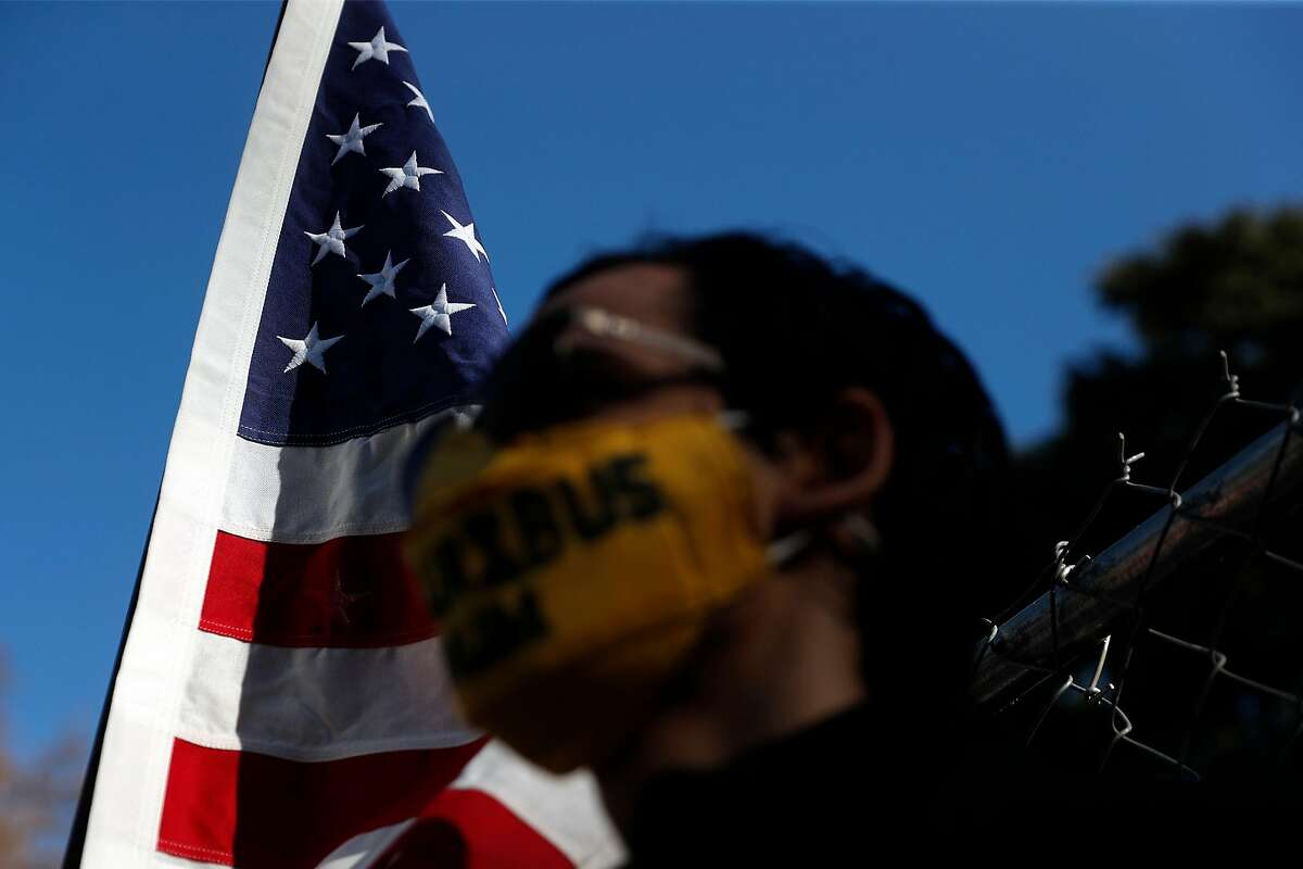 Christian Alvarado of Sacramento stands with an American flag outside the state Capitol on Jan. 17, 2021.
