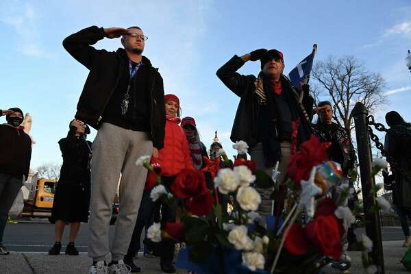 Tony Naples, left, and Gary Phaneuf salute at a memorial for Ashli Babbitt on Jan. 7, 2021, in Washington. Babbitt was shot and killed during the riot at the Capitol the day prior.