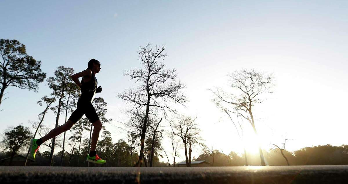A runner passes by during an in-person 50K race at Bear Creek Park, in Houston, Sunday, Jan. 17, 2021. Eighteen of Houston's most elite runners will be participating in the run. Many are running the virtual Houston Marathon, but five women are attempting to qualify for Team USA in the marathon distance. Callum Neff, unofficial race organizer and run coach, will attempt to break the Canadian record for the 50K (31 miles) distance that was set in February 1991, in Houston.