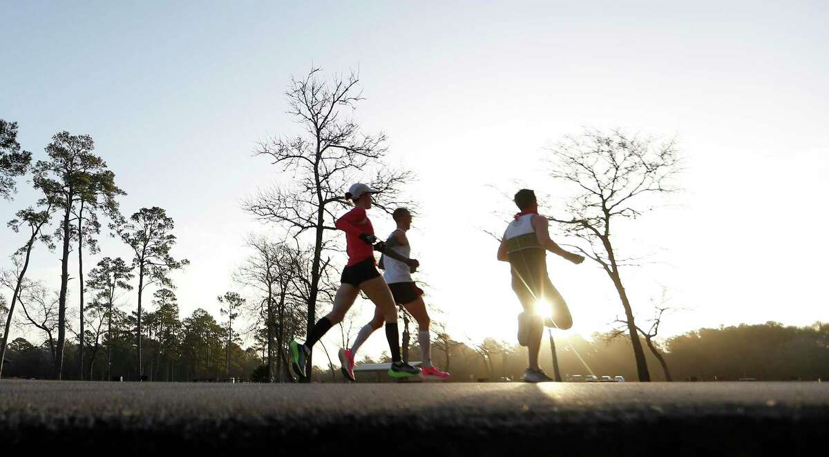 Runners pass by during an in-person 50K race at Bear Creek Park, in Houston, Sunday, Jan. 17, 2021. Eighteen of Houston's most elite runners will be participating in the run. Many are running the virtual Houston Marathon, but five women are attempting to qualify for Team USA in the marathon distance. Callum Neff, unofficial race organizer and run coach, will attempt to break the Canadian record for the 50K (31 miles) distance that was set in February 1991, in Houston.