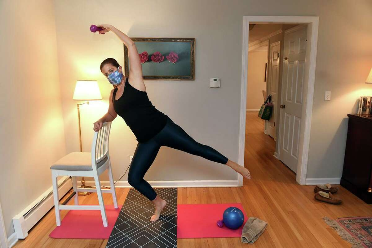 Ashley Palumbo of Open Barre with Ashley demonstrates one of the positions for her virtual fitness instruction in a corner of her dining room at home in Cheshire on Jan.15, 2021.