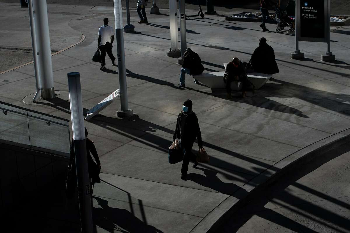 FILE -- People walk to a bus stop in downtown Denver, Colo., Dec. 30, 2020. After the White House declined to pursue a unified national strategy, governors faced off against lobbyists, health experts and a restless public consumed by misinformation. (Daniel Brenner/The New York Times)